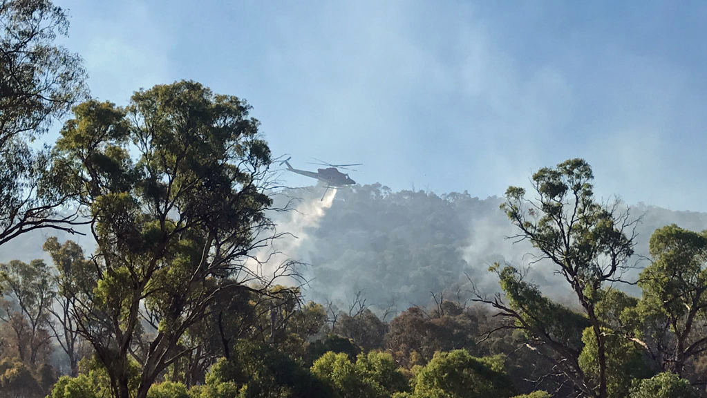 One of the ACT's water bombing helicopters drops water onto the fire at Booth. Photo by Steve Forbes.
